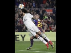 Real Madrid defender Marcelo (front) outjumps Barcelona midfielder Arturo Vidal for a header during their Copa del Rey semi-final first leg match at the Camp Nou stadium in Barcelona, Spain yesterday. (AP Photo/Emilio Morenatti)