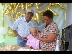 Mabel Goulbourne (centre) flashes a smile after cutting her birthday cake at a get-together her family hosted. She is joined by her nephew and niece.