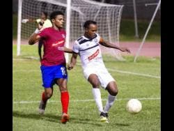 Ricardo Makyn Dunbeholden's Adrian Williams and Cavalier's Nicholas Hamilton (right) duel for the ball in their Red Stripe Premier League match at the Stadium East field on Sunday, December 16, 2018.