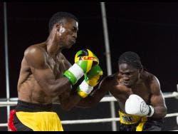 Kevin 'Buss Boy' Hylton (right) punishes opponent Toriano Nicholas with a right hook to the body at the Boxing Fightnight held at on the roof of Dunn's Electrical last Saturday.