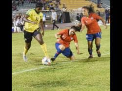 Khadija Shaw (left) of Jamaica dribbles past Chile's Cristiano Julio and Javiera Toro during their international friendly at the Montego Bay Sports Complex last night.