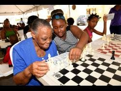 Ricardo Makyn photos Leanora Stewart, 73, a resident of Portia Simpson Miller Meadows, learns chess from 12-year-old Daisha Fraser. The occasion was the National Housing Trust's Social Development Department's introduction to chess initiative, a community intervention targeting youth, which started on Ash Wednesday. Members of the National Chess Club assisted with the teaching of the game.