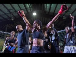 Lisa Frazer (centre) fighting out of Jamaica Defence Force (JDF)/ Wushinkido Lion Pride is declared the winner by referee Kasrie Cassells (second left) after defeating Shanice Blake (left) of Ruthless Sports Academy in the flyweight female title bout at Rough Fight League fight night held at the Douglas Orane auditorium at Wolmer's Boys School on Saturday March 9, 2019.