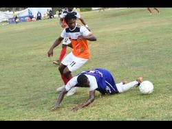 Shevan James (left) of Dunbeholden and Reno's  Renorio Downswell battle for the ball during the Red Stripe Premier League match between Dunbeholden and FC Reno  at  Royal Lakes Sports Complex on Sunday, March 10.