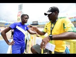 Buff Bay High coach Kevin Brown with female athlete Jamara Scott  at the National Stadium yesterday.