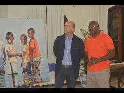 Josef Forstmayr (left), managing director of the Round Hill Hotel, admires the 'Boys in Water' art piece by artist Jeffrey Samuels (right) during an exhibition at the resort on Wednesday, March 20.
