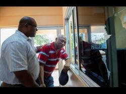 Gladstone Taylor  Following the murder of his daughter, Melford Clarke (right) is being consoled by Roy Notice, senior pastor at the Waltham Park New Testament Church of God on Waltham Park Road in St Andrew last week.