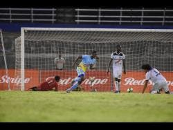 Andre Leslie (second left), of Waterhouse, celebrates his teammate Keammar Daley's goal scored in the second leg of their Red Stripe Premier League semi-final against Cavalier FC at the National Stadium in Kingston, yesterday.