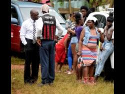 Onlookers gather at the scene where Shante Skyers's body was found in bushes near her home in Sterling Castle Heights, Red Hills, yesterday.