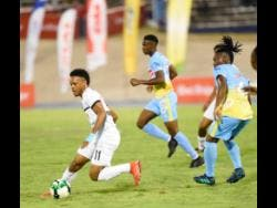 Cavalier FC's Alex Marshall (left) on the offensive against Waterhouse's FC's Keammar Daley (right) during their first leg Red Stripe Premier League semi-final game at the National Stadium on Monday, April 8. Waterhouse's Andre Leslie can also be seen tracking back in the background.