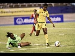 Jamaica's Khadija Shaw (right) attempts to go around Trinidad and Tobago goalkeeper Kimika Forbes during a CONCACAF Caribbean Women's Championships match at the National Stadium.