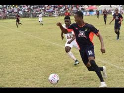 Ewan Barton of Faulkland FC attempting to dribble away from Falmouth United's Shaquan Reid in their JFF/Charley's JB Rum Super League first-leg semi-final at the Elleston Wakeland Centre in Falmouth, Trelawny, on Sunday. The game drew 1-1.