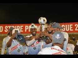 Members of the Portmore United team celebrate with the Red Stripe Premier League trophy after their 1-0 win over Waterhouse in the final at the National Stadium last night.