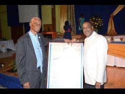 Alberga Foster (left) with Pastor Trevor Reid of the Orange Circuit of Seventh-day Adventist Churches in the West Jamaica Conference posing together with a citation that was given to Foster during a function held in his honour at the WJC Auditorium on May 5.