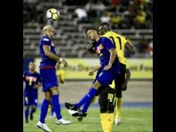 Jamaica's Cory Burke (right) rises above two Cayman Islands defenders to win a header during the team' CONCACAF Nations League game at the National Stadium.