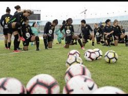 Members of Jamaica's Reggae Girlz squad stretch before the start of a training session at the National Stadium.