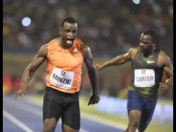 Jevaughn Minzie (left) wins the Men's 100m A race ahead of Nesta Carter at the Racers Adidas Grand Prix at the National Stadium last year.