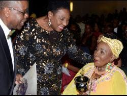 Ephraim Martin (left), organiser of the International Reggae and World Music Awards (IRAWMAs), and Olivia Grange (centre), minister of culture, gender, entertainment and sport, present Rita Marley with her IRAWMA award during the 37th staging at The Jamaica Pegasus hotel in New Kingston last Saturday.