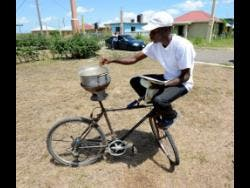 Ian Allen/Photographer John Dennis shows off his cooking skills on his bicycle in Springfield, Clarendon.
