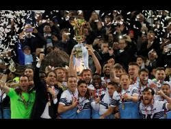 Lazio's Senad Lulic (centre) hold the Italian Cup aloft at the end of the final against Atalanta at the Rome Olympic Stadium yesterday.