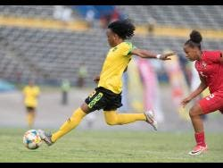Jamaica's Trudi Carter (left) drives a hard shot at goal ahead of Panama defender Katherine Castillo during their international friendly match at the National Stadium on Sunday.