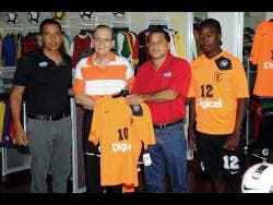 Howie Chin (second right), chairman of Locker Room Sports, presents a Tivoli Gardens match jersey to Edward Seaga (second left), president Tivoli Gardens Football Club in 2012.