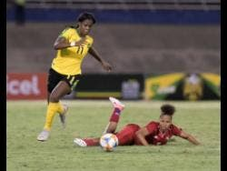 Reggae Girl Khadija 'Bunny' Shaw (left) dribbles to goal after beating Panama defender Yorima Pinzon during their international friendly match at the National Stadium on Sunday, May 19.