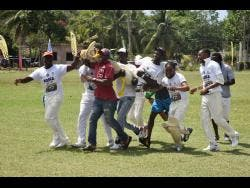 Players from Arcadia cricket team lifted Man-of-the-Match Keromie Austin off the field after hitting the winning run in their four-wicket win over Cambridge in their SDC / Wray and Nephew National Community T20 Cricket competition at the Dumfries Oval in St James.