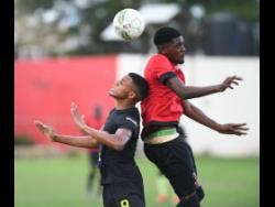 Ackeem Stewart (left) of Molynes United goes up for a header with Lime Hall player Mickalie McKoy in the JFF Premier league playoff at the  Constant Spring playfield on Sunday.