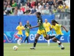 Khadija Shaw (left) dribbles the ball by Brazil midfielder Formiga yesterday in the FIFA Women's World Cup  Group C encounter between Jamaica and Brazil.