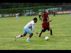 Peter Campbell of Faulkland FC dribbles by Kymani Gayle of Downs FC in their JFF Premier League play-off match at WesPow Park on Sunday, May 26, 2019.