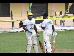 Petersville and Jamaica Scorpion's all-rounder Derval Green with his batting partner  Howard Jamieson in a SDC/Wray and Nephew T20 Community Cricket match at the Seaview Complex in Whitehouse, Westmoreland.