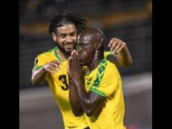 Michael Hector celebrates with  Dever Orgill after he scored his second goal as the Reggae Boyz beat Honduras 3-2 in their opening Gold Cup match at the National Stadium last night.