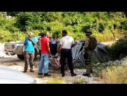 Police and military personnel at the murder scene in Green Pond, St James, where the body of 18-year-old Mark Powell Jr was discovered on Tuesday morning.