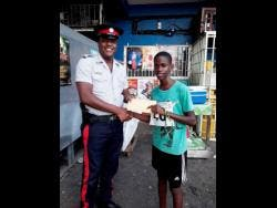 Constable Akeem Johnson (left) gives Jerome White money to buy sneakers after he finished 3k race while wearing flip-flops.