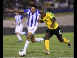 Jamaica's Dever Orgill (right) moves away from Honduran player Henry Figueroa in their Concacaf Gold Cup match held at the National Stadium on June 17. Jamaica won 3-2.