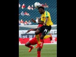 Jamaica's Shaun Francis (right ) leaps for the ball past Panama's Abdiel Arroyo.
