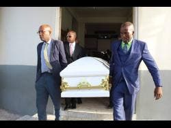 Pall-bearers take the coffin with the body of Gwendolyn Ramsay from the Seventh-day Adventist Church in Falmouth last Sunday.