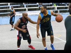 Kavarly Arnold  Levar Rose (left), then of Granville Jaguars, guards Vaughn Corke of Catherine Hall All-Stars in a 2018 game.