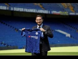 The new Chelsea manager, their former player Frank Lampard, poses for photographers with a club shirt by the pitch at Stamford Bridge stadium in London yesterday.