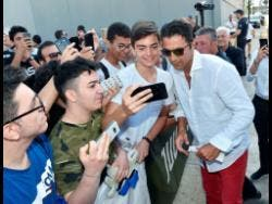 Italian goalkeeper Gianluigi Buffon poses for selfies with fans as he arrives to undergo medical tests at the Juventus Medical Centre in Turin, Italy, yesterday.