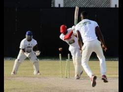 Travaine McIntosh (centre) of Johnson Mountain is bowled by Romario Halstead (right) Old Harbour during the Wray & Nephew/SDC National T/20 Community Cricket Competition at Chedwin Park in St Catherine, yesterday.