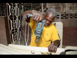 Douglas Lindo, who lost one of his legs two years ago, continues to work as a furniture maker.