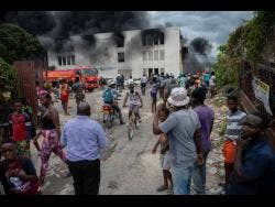 Scores of onlookers stare at the burning building.