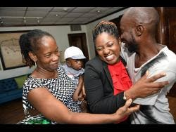 Tamara Blake (second right) is greeted by Suzette Whyte, mother of baby Sae'breon, and Sinclair Hutton, the child's father.