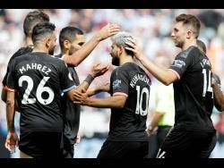 Manchester City's Sergio Aguero, center, celebrates after scoring his side's fourth goal from the penalty spot during the English Premier League soccer match between West Ham United and Manchester City at London stadium in London, Saturday.
