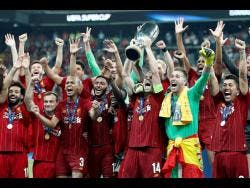 Liverpool's Jordan Henderson raises the trophy to celebrate with teammates after winning the UEFA Super Cup match between Liverpool and Chelsea, in Besiktas Park, Istanbul, yesterday.