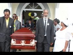 Pall-bearers carry the casket from the church after the thanksgiving service.