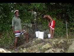 Billy (left) and Neville, two residents of  St Simon, also known as Fat Hog's Quarters in Hanover, catch water at a spring in the community .