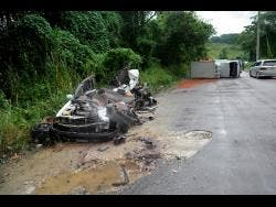 The remains of the Toyota motor car (left) driven by Collin Smith. In background is the truck that crashed into his vehicle.